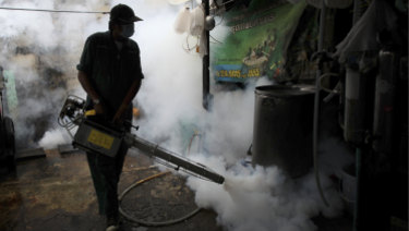 A Bangkok worker fogs a home with mosquito repellent after a Zika outbreak in 2013.