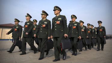 Military delegates arrive for a plenary session of China's National People's Congress (NPC) at the Great Hall of the People in Beijing, on Friday.