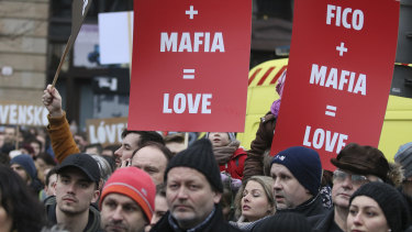 Demonstrators hold posters linking Slovakian Prime Minister Robert Fico to the mafia during an anti-government rally in Bratislava, Slovakia, on Friday.