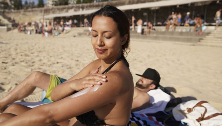 Serene Amaral from Waterloo applies some sunscreen at Coogee Beach on Sunday, when temperatures hit 38 degrees.