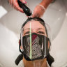 A woman wears a protective mask as she has her hair washed in London. Research indicates a headache is the most common symptom of the virus.