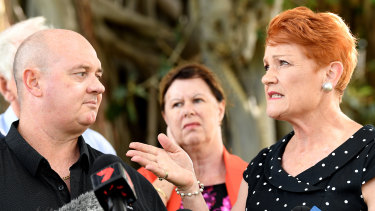Pauline Hanson gestures to Thuringowa candidate Mark Thornton after being questioned about postings on his sex shop's Facebook page during a press conference in Townsville.