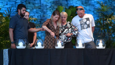 The family of Chris Sammut light a candle at the memorial service.