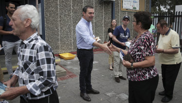 Every last vote: Steven Marshall hands out how-to-vote cards at a primary school on election day.