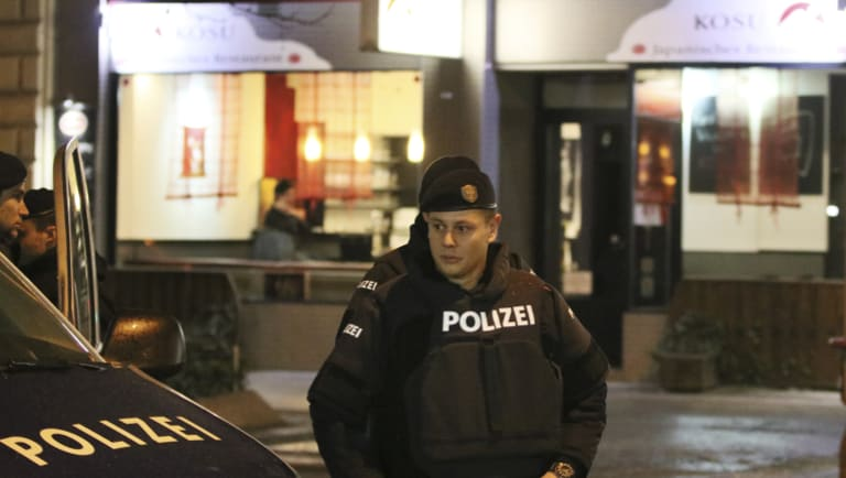 A police officers stands in front of a Japanese restaurant after several people were injured in a knife attack in Vienna on Wednesday.