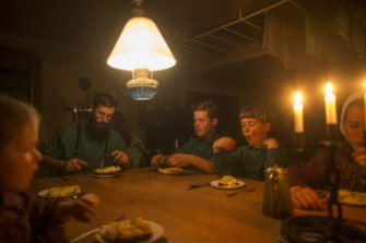 The McCallum family sits down to dinner by candlelight and  kerosene lamp.