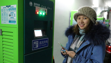 Young Beijing resident Dan Hong charges her new electric vehicle at a public charging station.