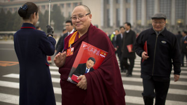 A delegate carries a magazine with a cover showing Chinese President Xi Jinping as he leaves the Chinese People's Political Consultative Conference.
