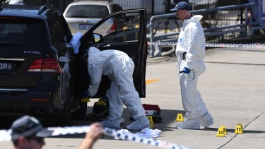 Police inspecting Hawi's bullet-ridden car.