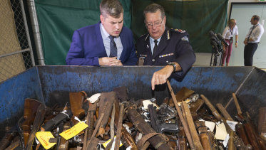 Police Minister Mark Ryan and Police Commissioner Ian Stewart inspecting some of the seized weapons, including rifles with scopes, shotguns and semi-automatic firearms.
