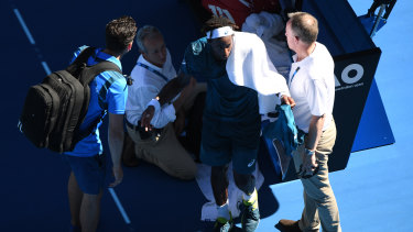 Gael Monfils of France is seen by doctors during his Australian Open match against Novak Djokovic.