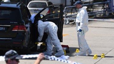 Police inspecting Hawi's bullet-ridden car.