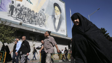 Iranian worshippers walk past a painting of the late revolutionary founder Ayatollah Khomeini and Basij paramilitary force members in Tehran.