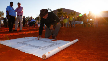 Noel Pearson signs a canvas on which the Uluru Statement from the Heart was later painted in May.