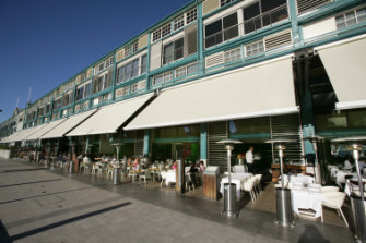 The restaurant strip at the finger wharf buzzes on a sunny autumn day.