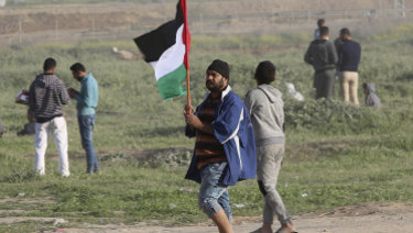 A protester waves his national flag during clashes with Israeli troops on the Israeli border with Gaza.