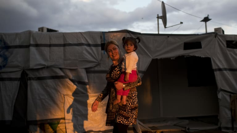 A Syrian woman carries a girl at the refugee camp of Ritsona about 86 kilometers north of Athens.