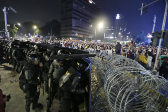 Riot police take defensive positions in central Jakarta.