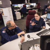 Reverend Paul McFarlane, senior chaplain for NSW Ambulance service, speaks with Rachel Moran, Dispatch Manager for West and Far West Regions at Sydney Control Centre