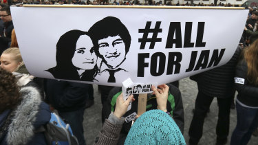 A woman sticks a sticker on a poster with a photo of slain journalist Jan Kuciak and his fiancee Martina Kusnirova, during an anti-government rally in Bratislava, Slovakia, Friday.
