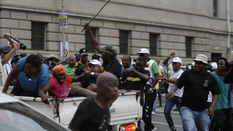 Members of the Black First Land First are attacked by African National Congress members protesting outside the ANC headquarters in Johannesburg on Monday.