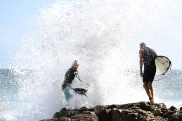 Surfers getting smashed by the big swell and high tides at Noosa on the Sunshine Coast on Friday.