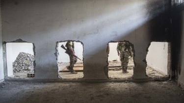 Members of the US-backed Syrian Democratic Forces (SDF) walk inside the stadium that was the site of Islamic State fighters' last stand in the city of Raqqa in October.