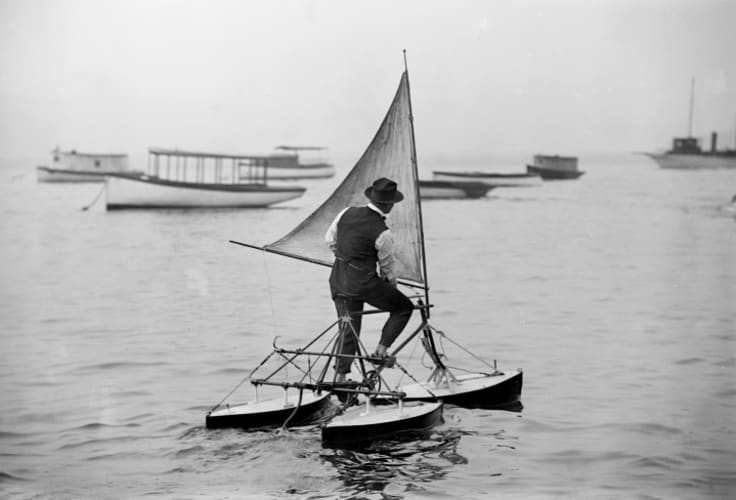 A man operates a water tricycle in the early 20th century.