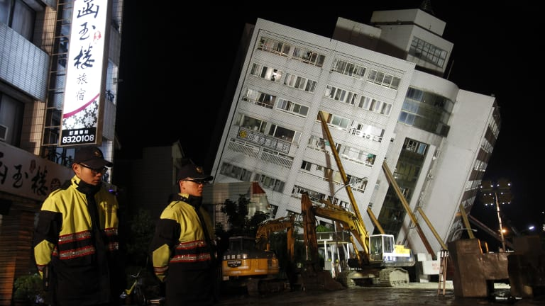 Two police officers guard outside of a collapsed apartment building in Hualien County, eastern Taiwan.