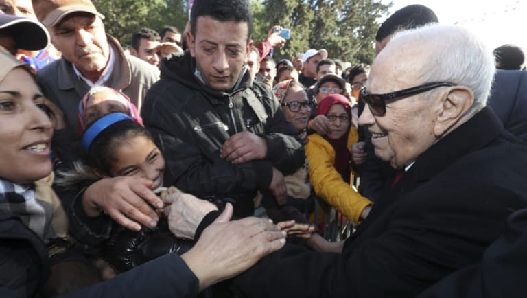 Tunisian President Beji Caid Essebsi shake hands with bystanders as he arrives for a event in Tunis, Tunisia, on Sunday, January 14.