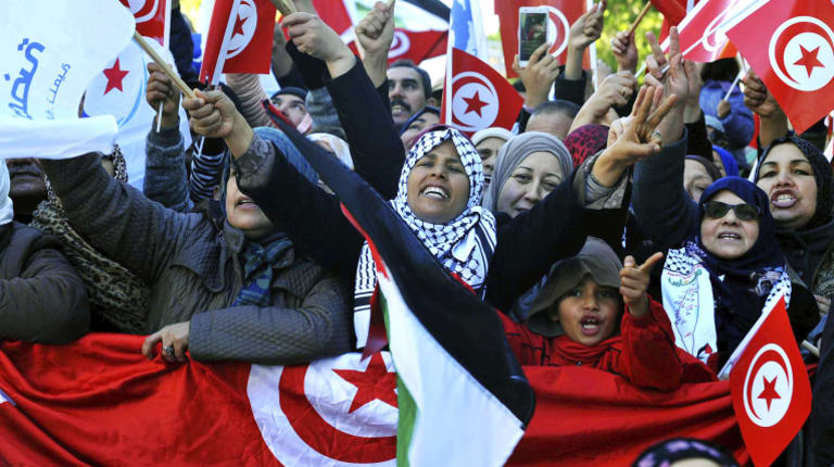 Tunisians march with national flags during a rally to mark seven years since revolution in Tunis on Sunday.