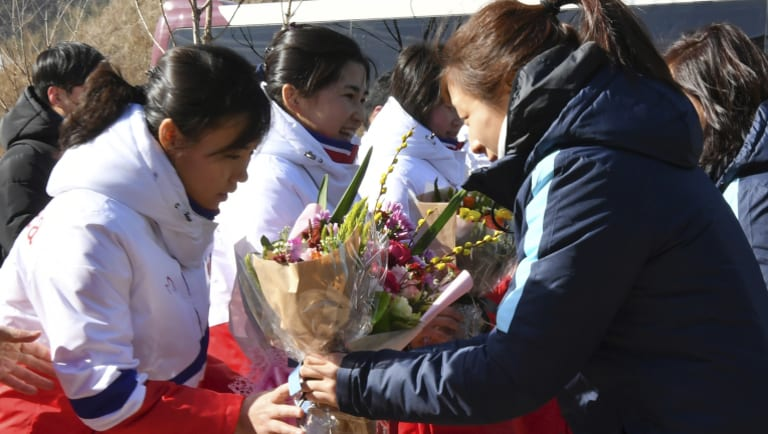 North Korean ice hockey players are greeted by their South Korean counterparts.