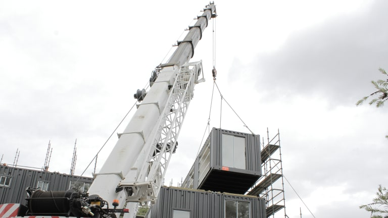 A crane lifts a module into place at Guildford.