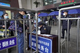Travellers are screened before entering the Wuchang Railway Station in Wuhan.