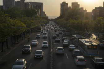 Traffic travel along a road in Beijing. The Chinese economy will grow by less than 2 per cent in 2020 as the anti-virus shutdowns combine with a collapse in global demand due to the pandemic, according to Bloomberg.