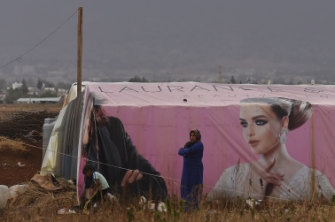 A woman stands in front of a temporary shelter as she watches children playing in an unofficial camp in the Bekaa Valley in Lebanon.