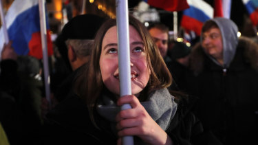 People wave Russian flags as they wait for election results in Manezhnaya square, near the Kremlin, in Moscow on Sunday.