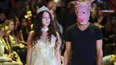 Sabrina Piper, 21, left, stands handcuffed to a male model costumed as a pig, during the #MeToo fashion show.