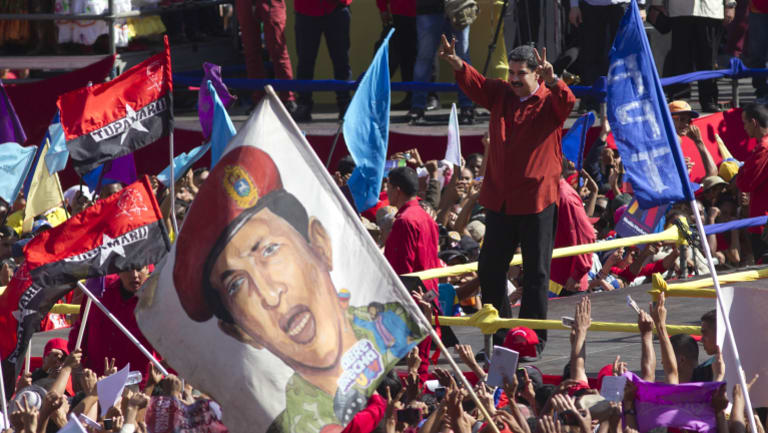 Venezuelan President Nicolas Maduro flashes victory signs after confirming he will run again.