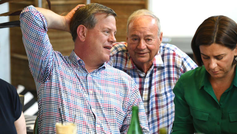 Opposition leader Tim Nicholls, flanked by his deputy Deb Frecklington, chats to his father Peter as he meets family and friends at a cafe in Brisbane on Sunday.
