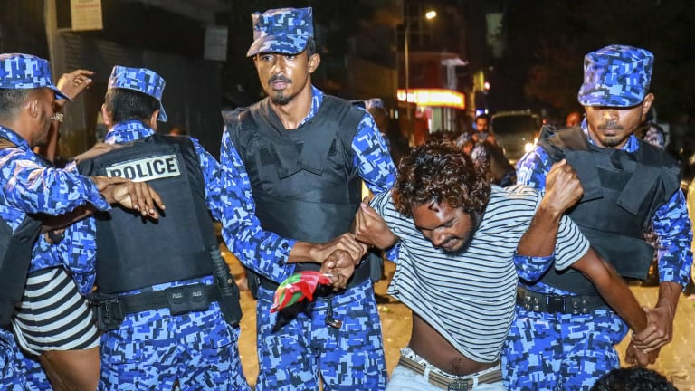 Maldivian police officers detain an opposition protester demanding the release of political prisoners during a protest in Male, Maldives.