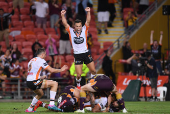 Bronco buster: Luke Brooks jumps for joy as Michael Chee Kam scores his match-winning try.