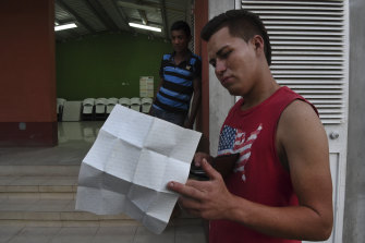 Ernesto, holding his ID papers, and friend Julio at Casa del Migrante in Flores. The pair escaped gang violence in Honduras.