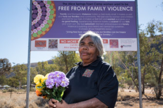 Helen Gillen and a family violence sign outside the Alice Springs town camps.