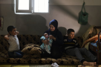 Syrian refugees Manal Hussein (second from right) holding two-month-old Omar Jalal. Ahmed, 12, is far right, in their brick shelter at Darashakran camp, Iraqi Kurdistan.
