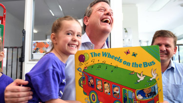 Five-year-old Lillian Mesic sits on Queensland Opposition Leader Tim Nicholls' lap as he visits a preschool in Woodhill.