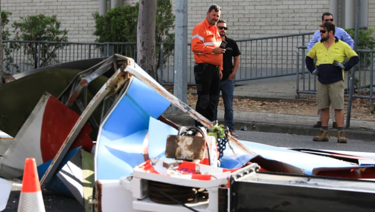 Workers survey the damage to a crane that tipped in Mitchelton, near the Brookside Shopping Centre.