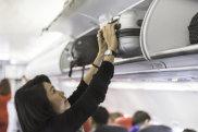 Woman putting cabin carry on bags luggage in plane overhead bin locker
