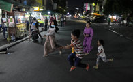 Children play in the middle of Sabang Street, a street food centre popular among locals and tourists in Jakarta.