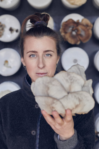 Barrett with a grey oyster mushroom grown on site at the Future Food System sustainability-showcase home in Federation Square.